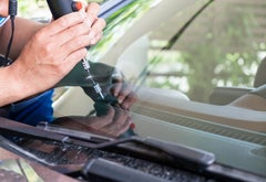 A person fixing a windshield on a car with a tool