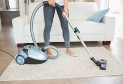 Woman hoovering rug in living room