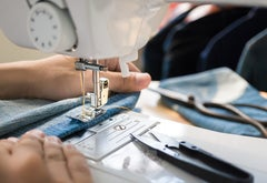 A person using a sewing machine on denim