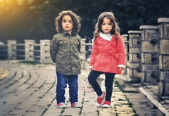 Two children standing outside on a stone walkway wearing coats