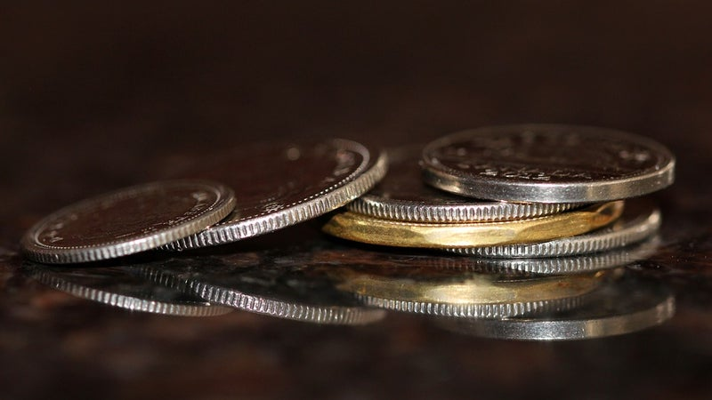 Six coins stacked on a reflective surface
