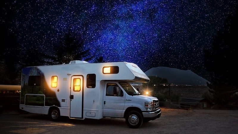 A travel trailer parked at night with stars visible