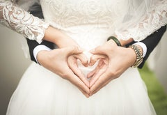 A couple's hands in the shape of a heart, wearing wedding attire