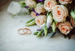 Two wedding bands on a marble surface next to a bouquet of flowers