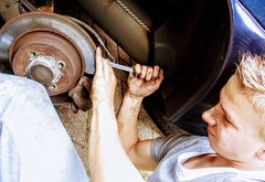 A young man using a wrench to work on a car