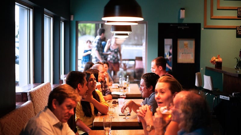 People sitting at tables in a dimly lit restaurant