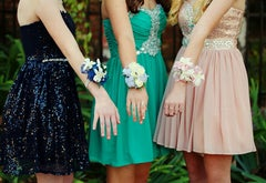 Three girls in dresses with wrist corsages