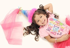 Young girl with a birthday hat and shirt on