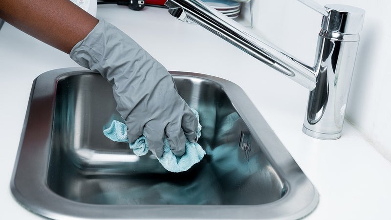 A person wearing gloves cleaning a sink