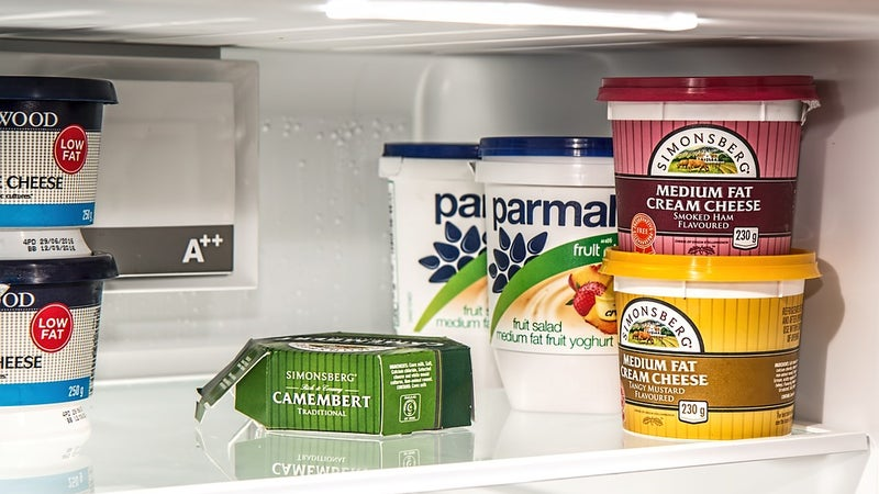Multiple food items on a glass refrigerator shelf