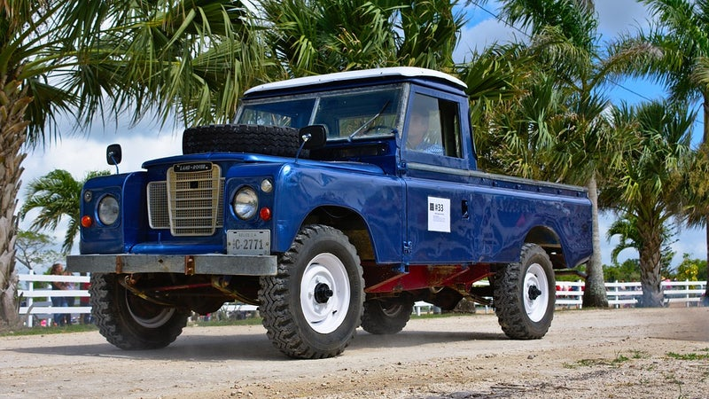 A vintage blue Toyota Land Rover on a gravel road