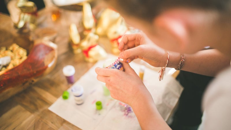 A girl crafting using beads and glue